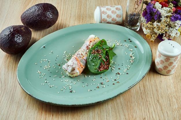 キノア、ニンジン、ほうれん草、木製のテーブルの上の青い皿にベジタリアン春巻き。タイの屋台。フィットネスと健康的な食事。閉じる。