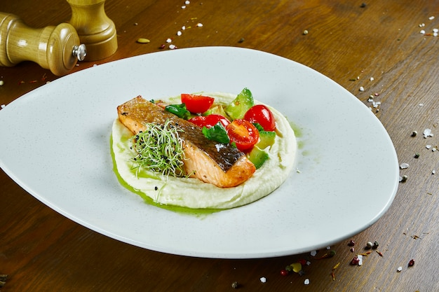 Сочный стейк из лосося на белой тарелке с гарниром из картофельного пюре, авокадо и помидоров черри с зеленым соусом. деревянный стол. крупным планом на вкусный ресторан морепродуктов