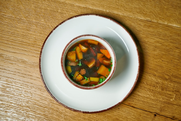 木製のテーブルの上の白いボウルに野生のキノコのスープ。上からの眺め。健康的な食事。ベジタリアン料理