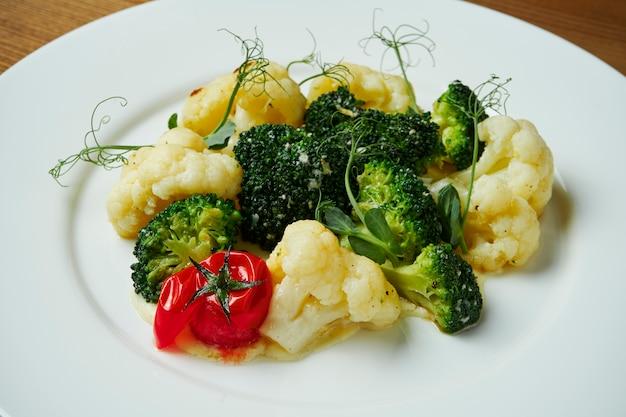 白い皿にクリームソースと蒸しカリフラワーとブロッコリーのビューを閉じます。健康的な食事。ビタミン入りの食品。ベジタリアン