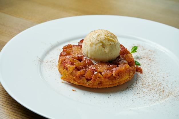Крупным планом вид на вкусный яблочный пирог с тающим мороженым на белой плите на деревянном столе. свежая и вкусная выпечка.