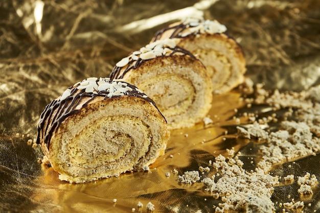 Запеченные рулетики с халвой и миндалем на синюю тарелку на золотом столе. турецкие сладости чай или кофе пекарня