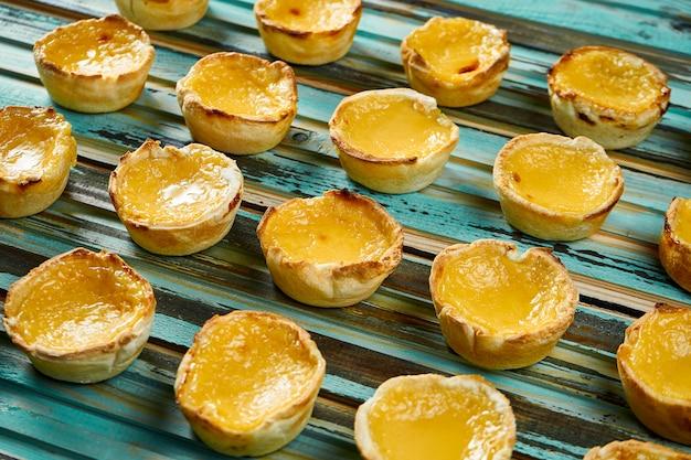 おいしいパステルデナタ-木製のテーブルにシナモンをまぶしたポルトガルカスタードエッグタルトペストリーのビューを閉じます。ベーカリー。