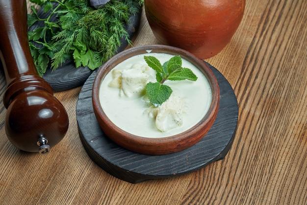 Гебжалия - грузинская закуска, хинкали из теста с зеленью в соусе мацони и сулугуни в керамической миске на деревянной поверхности