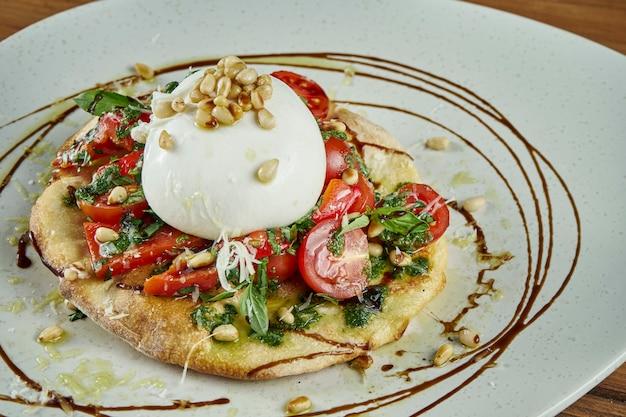 Крупным планом вид на итальянский сыр буррата с соусом фокаччо, помидорами, базиликом и орехами. ресторанное блюдо на деревянном столе. крупным планом зрения. еда плоская планировка
