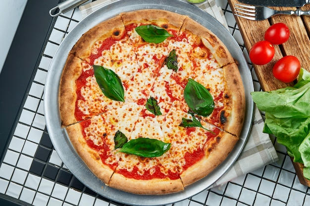 モッツァレラチーズ、トマト、バジルのクラシックなマルガリータピザ。白いテーブルの成分と組成のイタリアのピザ。上面図。食品フラットレイ