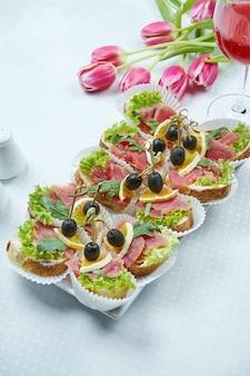 Питание - канапе со свежим тунцом и рукколой в керамической тарелке.