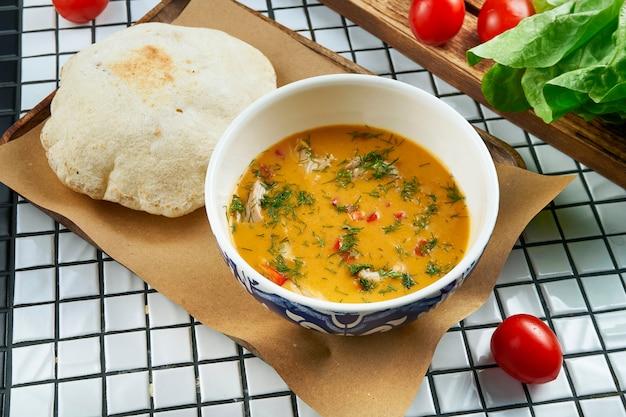 白いテーブルに羊皮紙で提供しています美しいセラミック弓でフォカッチャのパンとおいしいレンズ豆のクリームスープのビューを閉じる