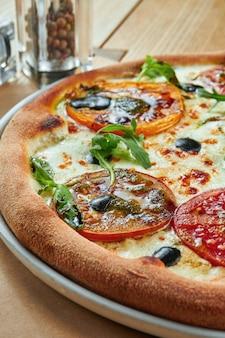 Аппетитная запеченная пицца с плавленым сыром и различными видами помидоров с хрустящей корочкой на деревянном столе. ресторан обслуживает. пицца маргарита
