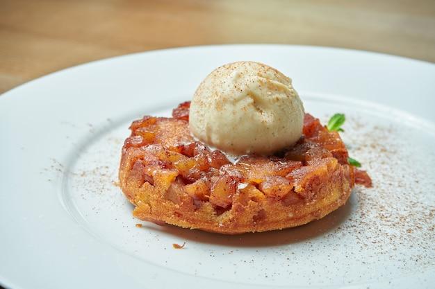 Свежеиспеченный яблочный пирог из песочного теста с шариком мороженого на белой тарелке на деревянном столе. вкусная выпечка на завтрак