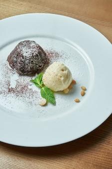 Шоколадная помадка с шариком ванильного мороженого на белой тарелке на деревянном столе. аппетитный десерт на завтрак