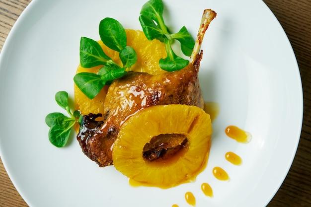 木製のテーブルの白いプレートにパイナップルと甘いソースと鴨のコンフィを焼き。お祝いの夕食のためのおいしい肉。トップビューの食べ物。フランス料理