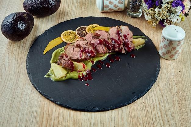 木製のテーブルの黒いプレートにマッシュアボカドと甘いベリーソースのおいしい焼き鴨フィレのビューを閉じます。お祝いの夕食のためのおいしい肉。