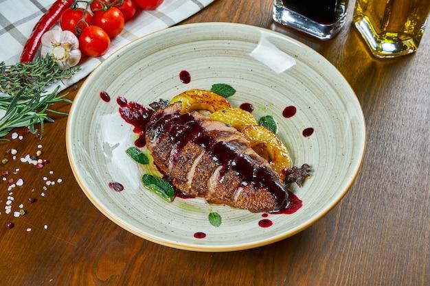 木製のテーブルの白いプレートにパイナップルと甘いベリーソースのおいしい焼き鴨フィレのビューを閉じます。お祝いの夕食のためのおいしい肉。