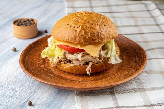 Свежий и вкусный бургер с ростбифом, помидорами, листьями салата и сыром на синем фоне деревянные. американский традиционный фастфуд. продовольственная фото фон.