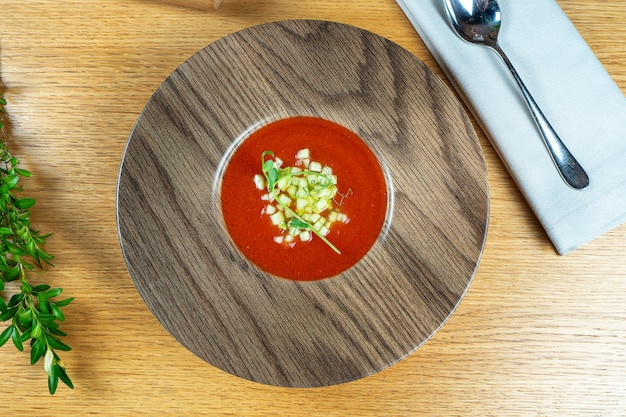 伝統的なガスパチョスープの平面図です。木製の木製ボウルに赤い冷たいスペインのスープ。地中海料理。トマトスープ。昼食
