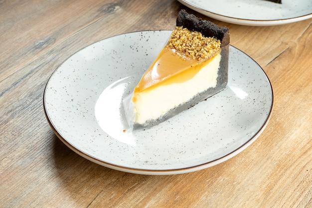 白いプレート上の繊細な風通しの良いキャラメルチーズケーキのスライスを閉じます。夕食後に美味しいデザートケーキ。