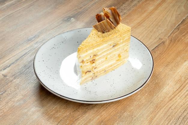 Крупным планом вид на вкусный кусочек медового торта на белом фоне на деревянных фоне. вкусный кремовый торт. сладкий десерт после обеда.