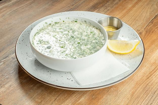 オクローシカとボウルにクローズアップ。さまざまなハーブと細かく刻んだ肉や魚を使ったクワスまたは血清で作った冷たいスープ。ロシア料理。