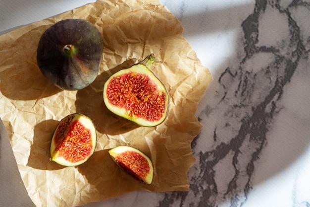 Вид сверху свежей экзотики вырезанный на половину инжира на крафт-бумаге мраморный стол