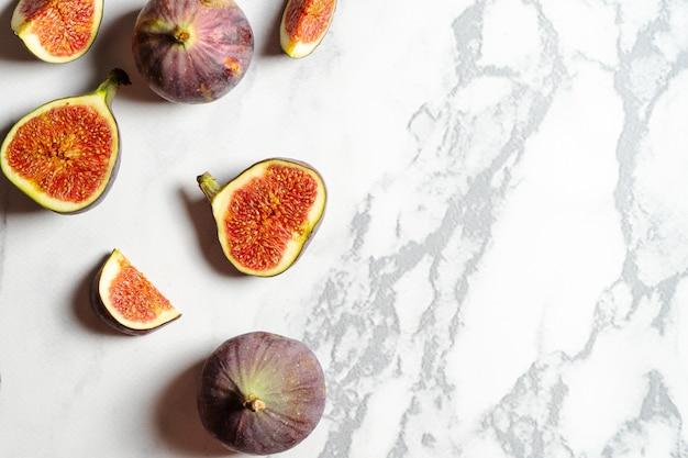 Вид сверху свежей экзотики вырезанный на половину инжира на мраморном столе.