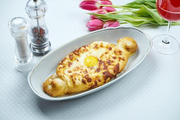 Крупным планом на вкусный традиционный аджарский хачапури - открытый запеченный пирог с плавленым сыром (сулугуни) и яичным желтком. традиционная грузинская еда. ресторанное обслуживание