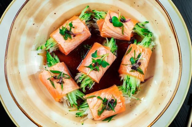 サーモン、マイクログリーン、キュウリの創作巻き寿司のクローズアップ。暗い背景に醤油と黄色のボウルでおいしいサーモン刺身。日本料理。シーフード、生の魚。