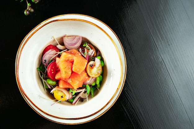 Салат из лосося севиче с помидорами черри, листьями салата, зеленой фасолью, луком и помидорами черри. салат из свежих морепродуктов.
