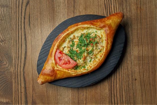 Вид сверху на вкусный традиционный аджарский хачапури - открытый запеченный пирог с сыром (сулугуни), говядиной и яичным желтком. традиционная грузинская еда. ресторанное обслуживание
