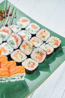 盛り合わせロールと白い木製の背景に分離された緑の皿の上の寿司のセットのビューを閉じます。サーモン、うなぎの寿司。日本の寿司料理