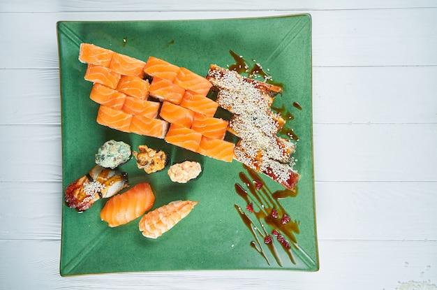 盛り合わせロールと白い木製の背景に分離された緑の皿に寿司のセットの平面図です。サーモン、うなぎの寿司。日本の寿司料理
