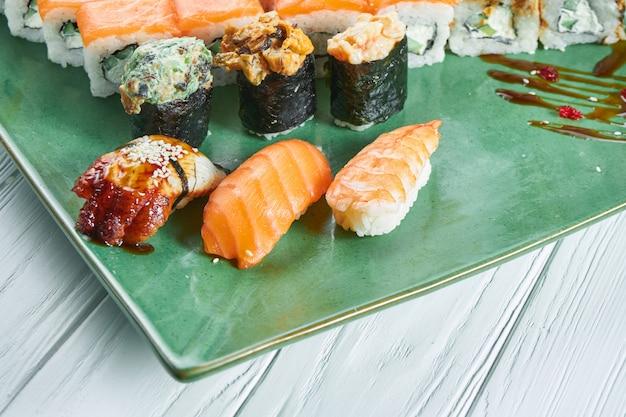 白い木製の背景に分離された緑の皿に各種寿司のセットのビューを閉じます。サーモン、うなぎの寿司。海老の寿司