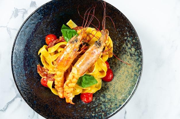 Домашняя итальянская паста с помидорами черри и морепродуктами. паста со свежими и вкусными креветками-лангустинами в темной стильной миске на мраморном столе.