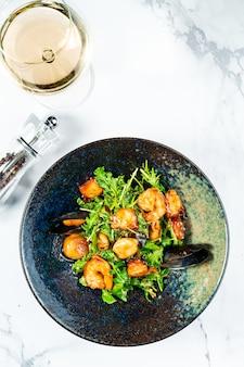 Теплый салат из морепродуктов в стильной черной миске на мраморном столе. салат из морских гребешков. мидии, креветки в кисло-сладком соусе.