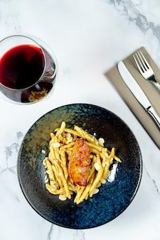 Оригинальная итальянская паста с печенью фуа-гра в стильной черной миске на мраморной тарелке