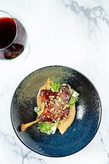 大理石のテーブルのスタイリッシュなダークボウルに、アヒルの足にピーナッツバターとドーブルーチーズを合わせます。グルメランチ料理。フランス料理。