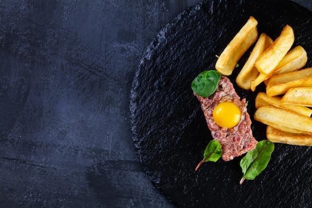 Закройте вверх по взгляду на вкусном стейке тартар из говядины, который служат с яичным желтком, погружением картошки на черной каменной плите на темной предпосылке.