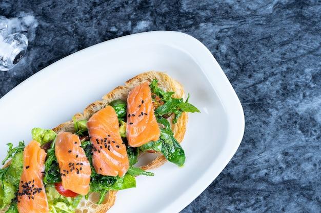 サーモン、レタス、チェリートマト、大理石のテーブルのソースとおいしいイタリアのブルスケッタのビューを閉じます。イタリア料理。