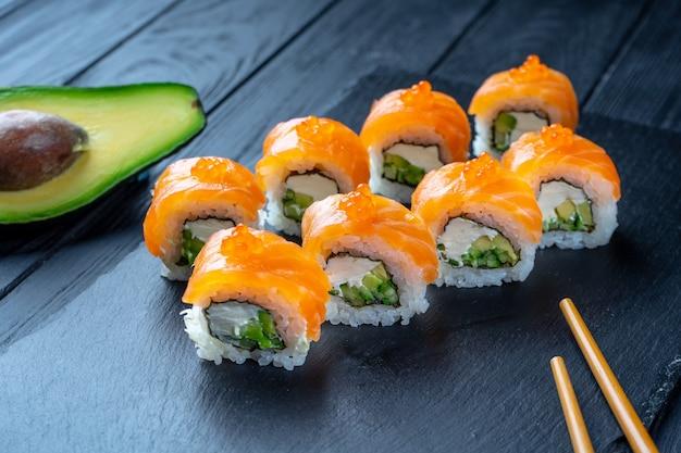 クリームチーズとサーモン、キャビアの巻き寿司を閉じます。コピースペースを持つ黒い木製の壁に石の暗いプレートに寿司。日本の食べ物。シーフード。ダイエット、健康食品。フィラデルフィア