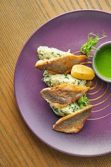 Панированное жареное филе сибаса с рисом гарнир на фиолетовую тарелку на деревянном столе. ресторан обслуживает. крупным планом, селективный фокус