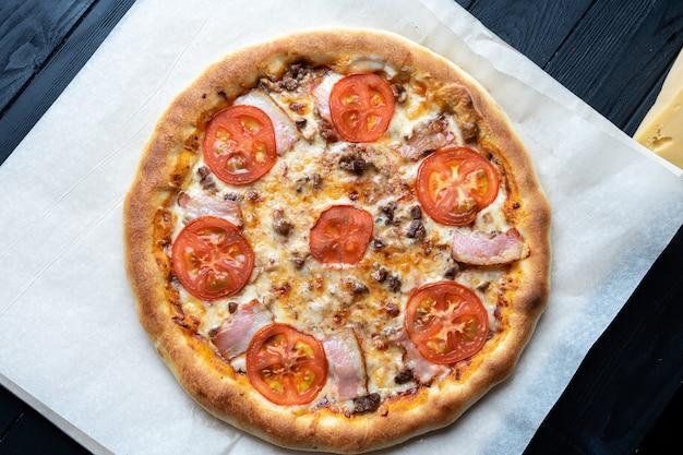 黒いテーブルの上のクラフトペーパーで平面図のおいしいピザ。ハム、トマト、マッシュルームのピザ。イタリア料理。フードフォトテーブル