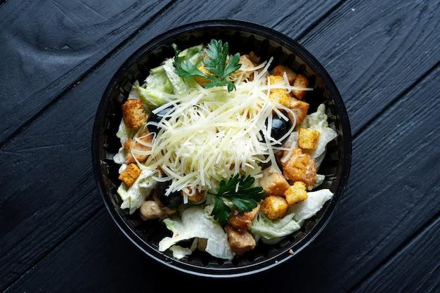 Салат цезарь с гренками, листьями салата, оливками и курицей в пластиковой миске на темном столе. доставка еды в офис. офисный обед.