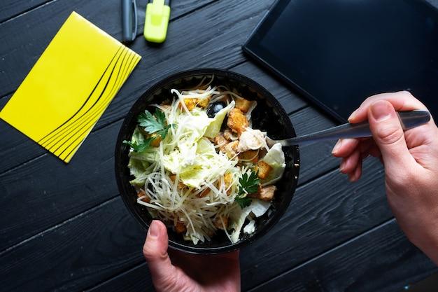 Салат цезарь с гренками, листьями салата, оливками и курицей в пластиковой миске на темном столе. доставка еды в офис. офисный обед. рабочий стол с салатом, ноутбуком и планшетом