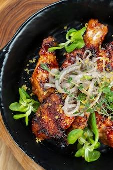 Жареные куриные крылышки в медово-пивном соусе подаются на декоративной сковороде с зеленью. крупным планом, селективный фокус. деревянная стена. пищевое фото