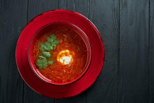黒い木製のテーブルの上にボウルにサワークリームと自家製のおいしいウクライナボルシチ。ウクライナ料理。宇宙食写真をコピーします。赤いスープ