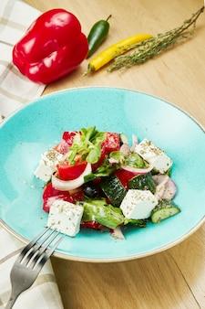 Греческий салат с оливками, помидорами, сыром фета, луком в синей миске на деревянной стене. закройте выборочный фокус
