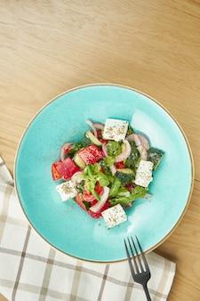 Греческий салат с оливками, помидорами, сыром фета, луком в синий шар на деревянный стол. закройте выборочный фокус