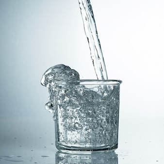 Свежая и холодная, чистая вода наливается в стакан. очищенная вода в стакане на сером столе. движение заморозить всплеск кристально чистой водой на сером столе.