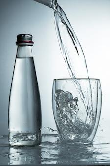 Свежая и холодная, чистая вода наливается в стакан с бутылкой. очищенная вода в стакане на серой стене. движение заморозить всплеск кристально чистой водой на серой стене.
