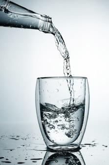 Свежая и холодная, чистая вода наливается в стакан. очищенная вода в стакане на серой стене. движение заморозить всплеск кристально чистой водой на серой стене.